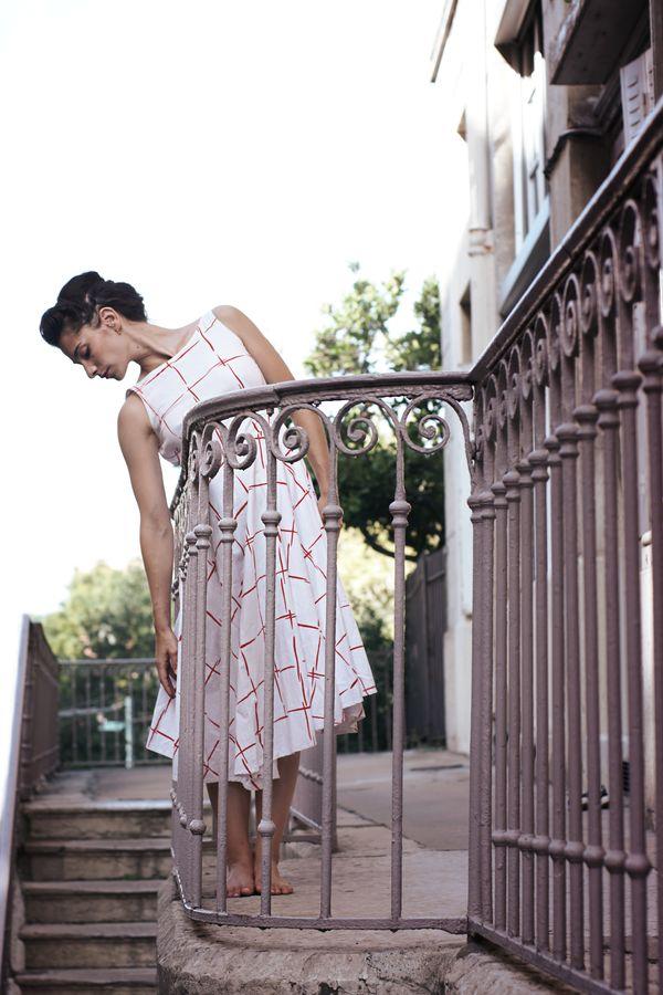 Mathilde fait de la danse contemporaine en robe rouge et blanc, à motifs carrés, à la Croix-Rousse. Elle se laisse aller contre la rampe de l'escalier.