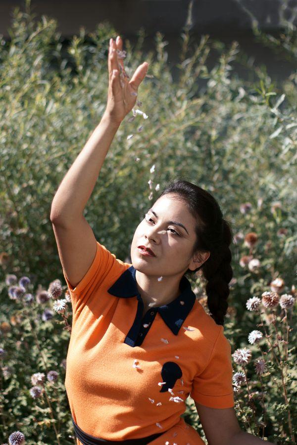 Ana en tenues vintage de la friperie les Jupons de Paulette pose pour une affiche de propagande des années soixante pour un monde meilleur.