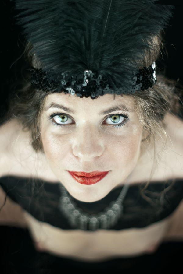 Alix Betty en tenue de danseuse de cabaret Charleston lève les yeux. Elle porte une plume dans les cheveux comme il était coutume dans les années 20.