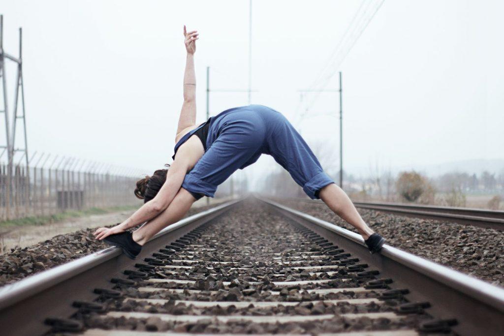 Laura fait de la danse contemporaine en bleu de travail sur une voie ferrée, à Beynost dans l'Ain. La danseuse entre les rails pointe son doigt vers le ciel.