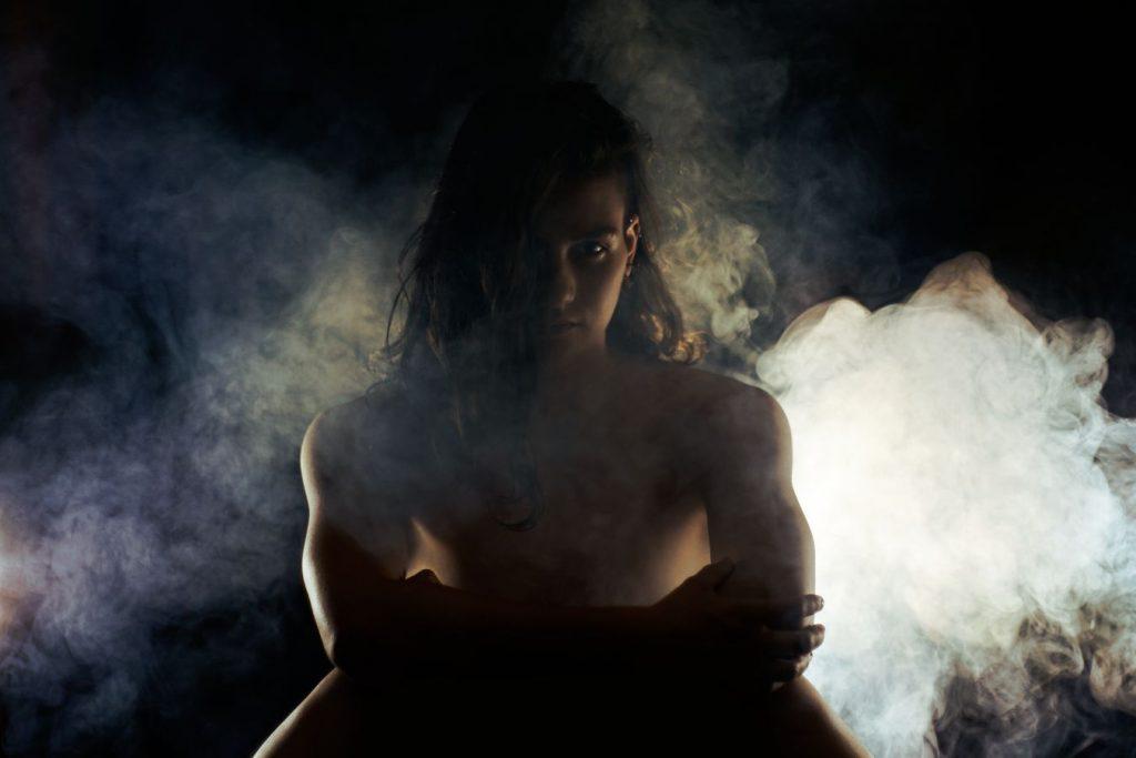 Portrait de Lisa, nue assise dans la fumée, en studio, chez moi à Caluire-et-Cuire. Le contre-jour fait, alors ressortir sa musculature de trapéziste.
