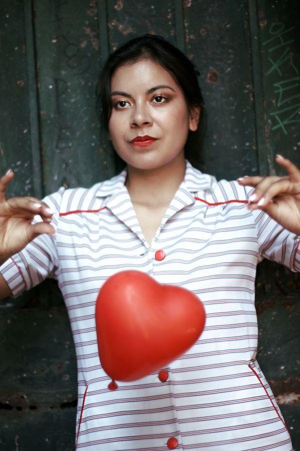 Ana porte une robe vintage à rayure de la friperie les Jupons de Paulette. Un ballon rouge en forme de cœur tombe devant elle.