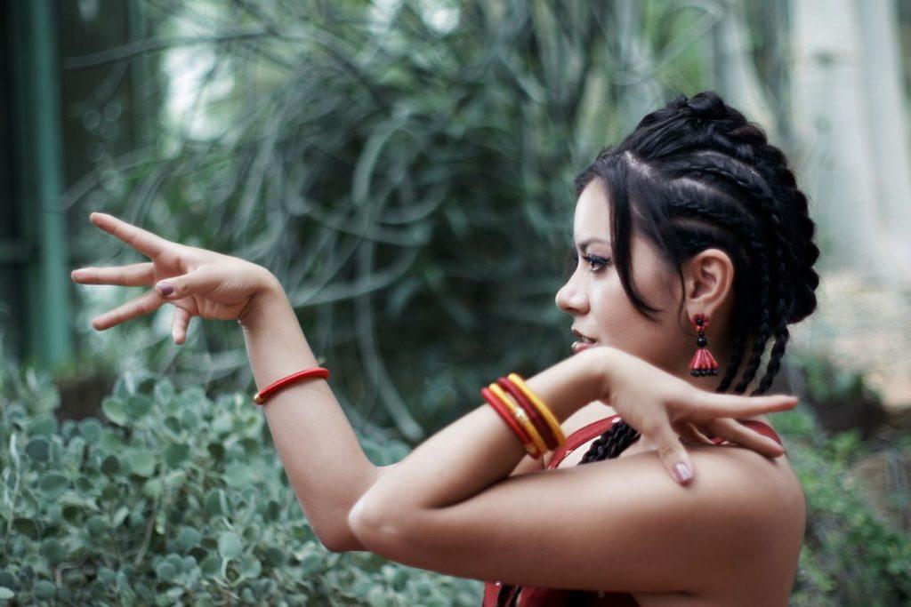 Dans les serres africaines du parc de la Tête d'Or à Lyon, Ana joue avec ses mains. Elle est parée de vêtements et bijoux indiens.