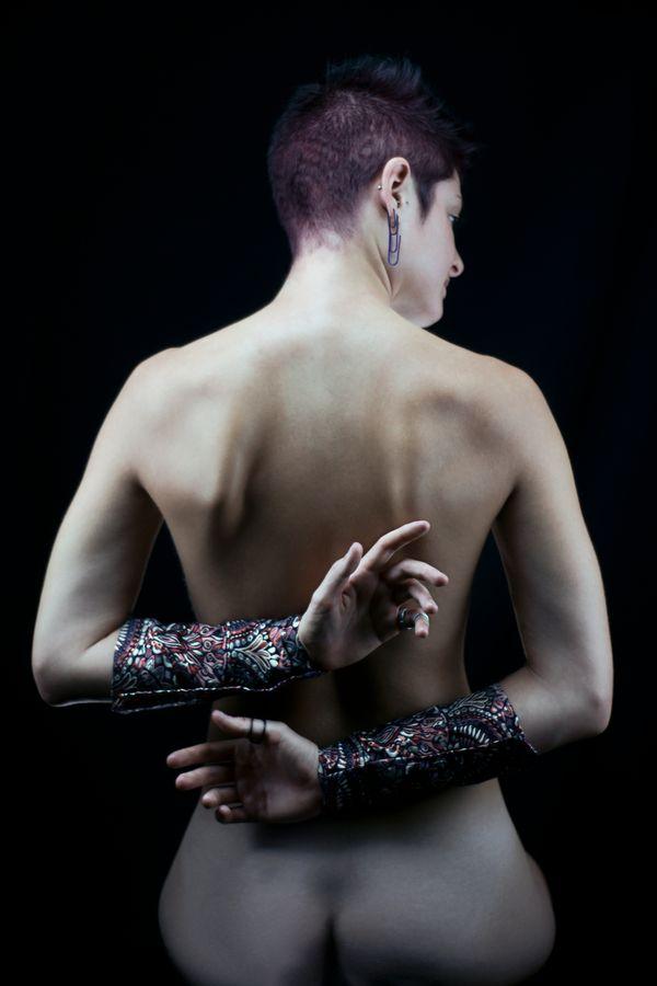 Portrait de Purple Johanna, nue de dos. Elle a les bras dans le dos, recouverts de manchons bordeaux assortis à la couleur et aux motifs de ses cheveux.