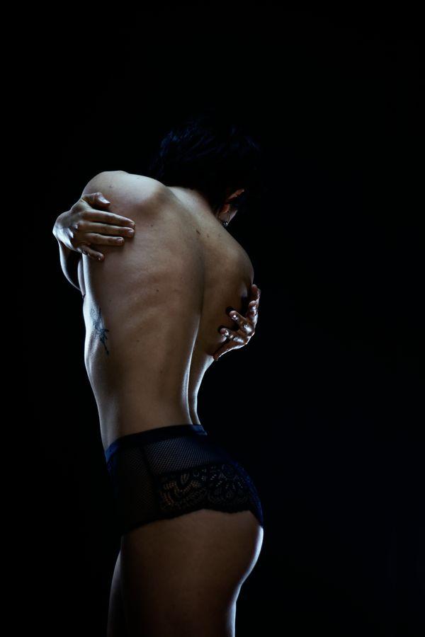 Portrait en studio de Iona, de dos, en lingerie. Son corps, tout en torsion laisse apparaître un tatouage dans la lumière.