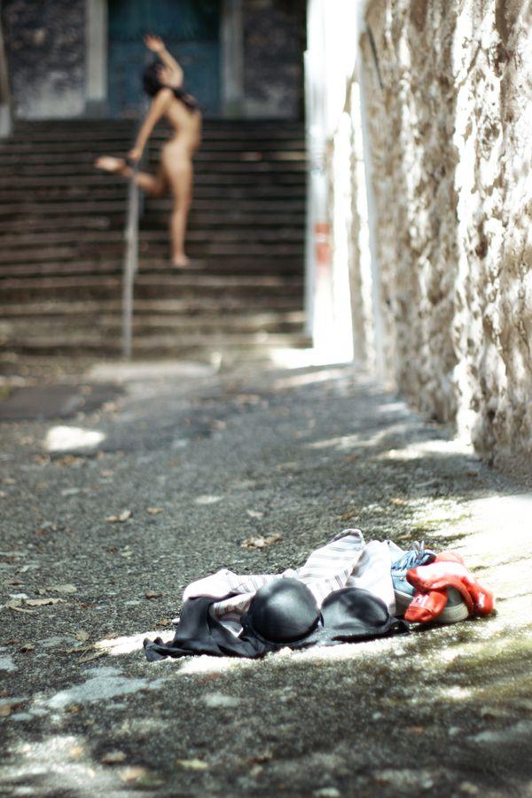 Au sol, des vêtements ont été abandonnés. Au loin, la silhouette nue et floue d'Ana danse en toute liberté dans un escalier en ville.