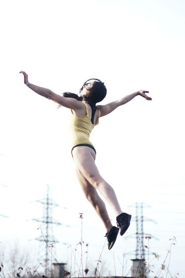 Laura saute et fait de la danse contemporaine au petit matin à Beynost, dans l'Ain. Elle s'élance dans les airs dans les rayons montants du soleil.