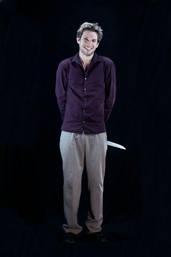 Portrait d'un farceur en studio, chez moi à Caluire-et-Cuire. Max, espiègle tient un couteau dans son dos et nous présente un large sourire innocent.