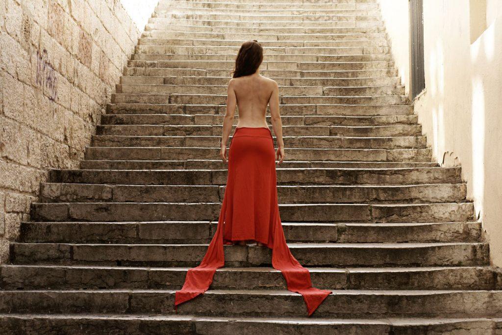 Portrait, de dos de Mathilde dans le passage Thiaffait, à la Croix-Rousse, à Lyon. La danseuse a défait le haut de sa robe rouge et dévoile son dos.