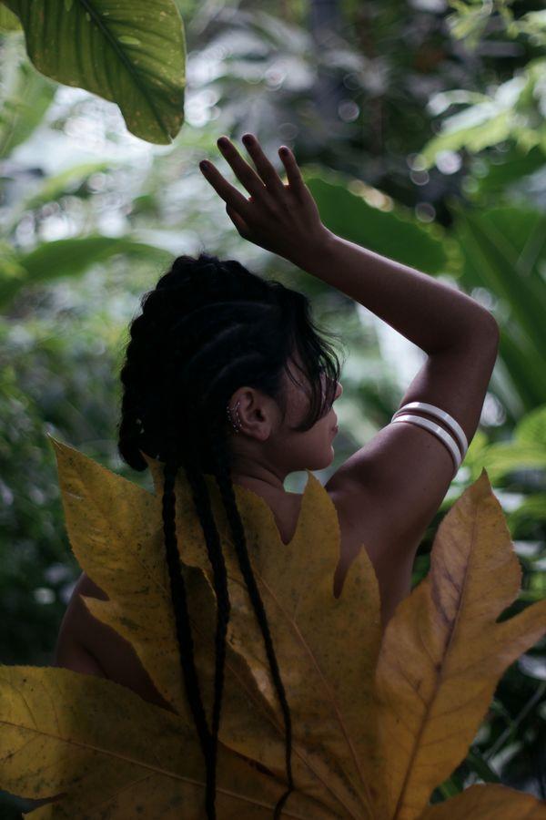 Portrait de dos, d'Ana dans les serres tropicales du Parc de la Tête d'Or, à Lyon. Derrière elle, elle est tient une immense feuille jaune.
