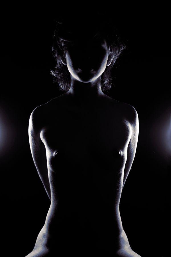 Louise, assise nue se tient parfaitement droite dans les lumières du studio. L'éclairage en contre-jour transforme, alors son corps en statue.