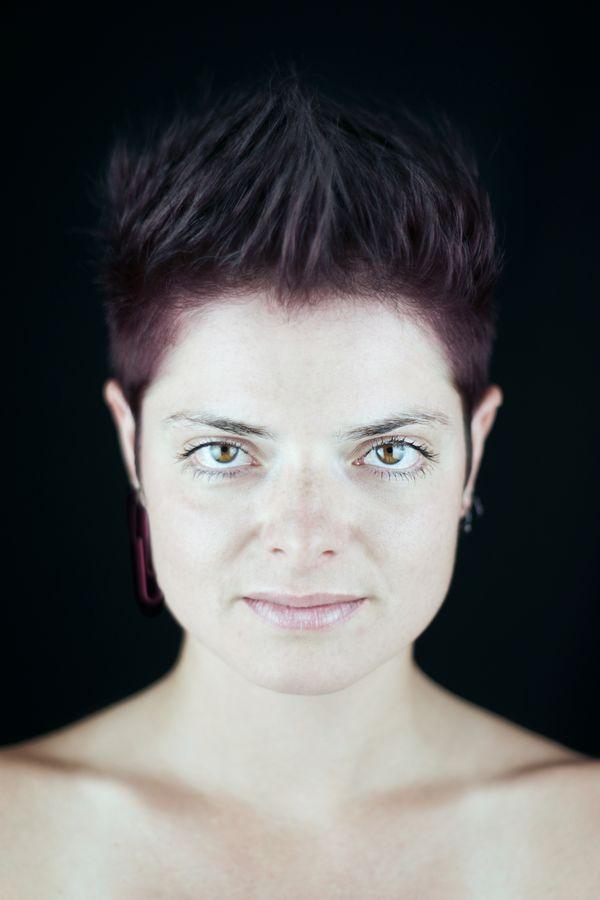 Portrait serré de Johanna et ses cheveux pourpres. Bien que sur fond noir, ce portrait est high key. La couleur de ses yeux ressort particulièrement bien.