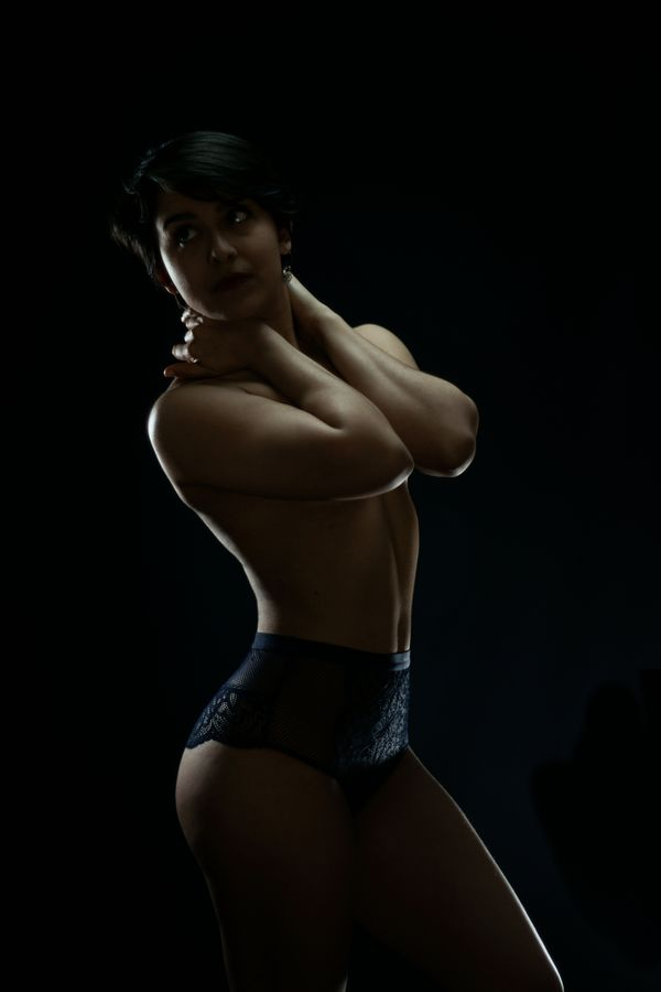 Portrait de Iona en studio, à Caluire-et-Cuire. Dans un clair-obscur, sa silhouette en lingerie émerge du noir. Elle cache sa poitrine avec ces bras.