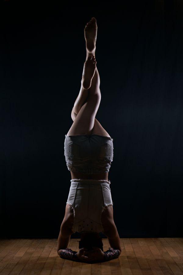 Johanna fait un équilibre en trépied dans les lumières de mon studio, sur mon parquet à Caluire-et-Cuire. Ses jambes sont enroulées l'une autour de l'autre.