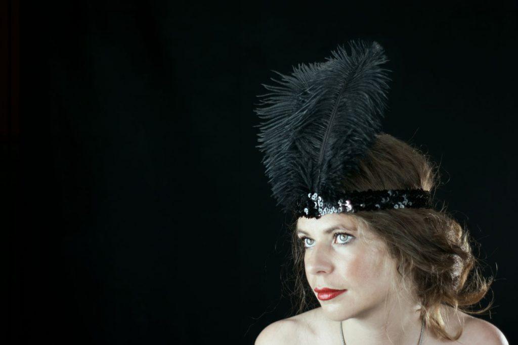 Alix Betty porte une coiffure de danseuse des années 20. Dans les loges du cabaret charleston, elle semble attendre le début du spectacle.