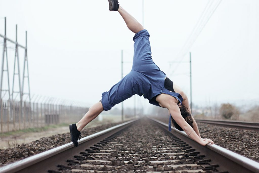Laura fait de la danse contemporaine sur la voie ferrée à Beynost, dans l'Ain. Elle porte une salopette bleue et son pied sort du cadre.