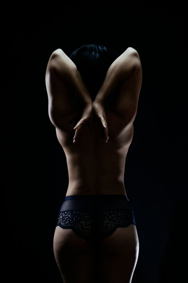 Iona, de dos en lingerie avec les bras relevés derrière sa tête comme des ailes. Portrait en clair-obscur, en studio, chez moi à Caluire-et-Cuire.