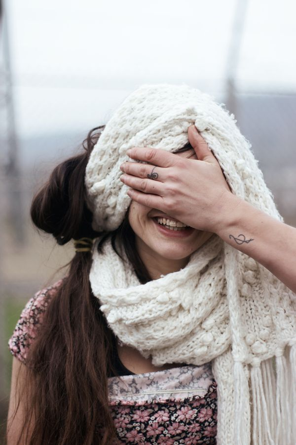 Silly portrait de Laura qui se masque le visage avec sa main, ne dévoilant que son sourire. La danseuse a enroulé une grande écharpe blanche autour de sa tête.
