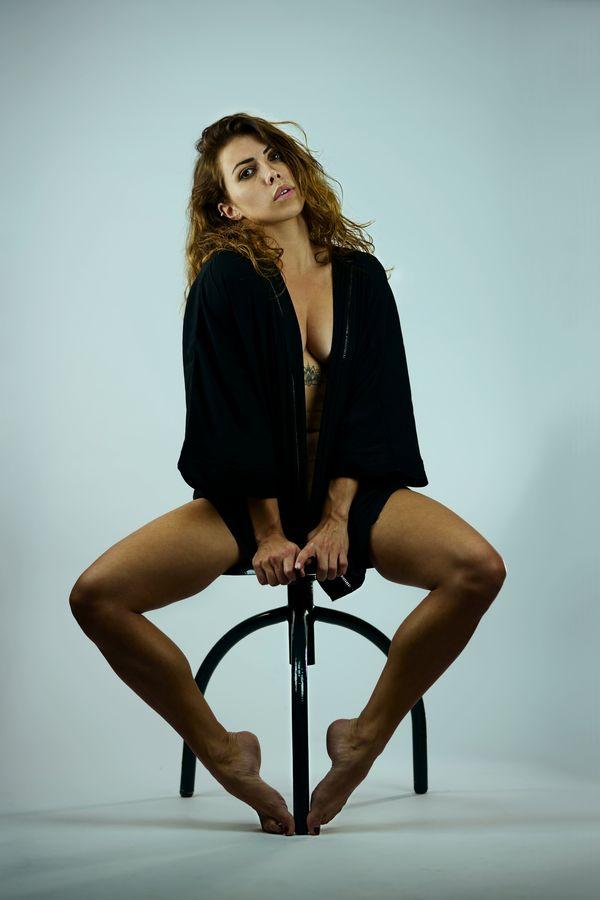 Portrait d'Anaïs assise sur un tabouret, en studio, à Caluire-et-Cuire. Elle porte une veste noire qui révèle son tatouage en dessous de la poitrine.