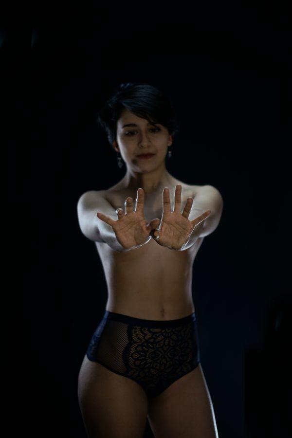 Portraits des mains de Iona, paumes ouvertes tendues vers nous. Ses mains, qui attrapent la lumière, cachent, alors sa poitrine.