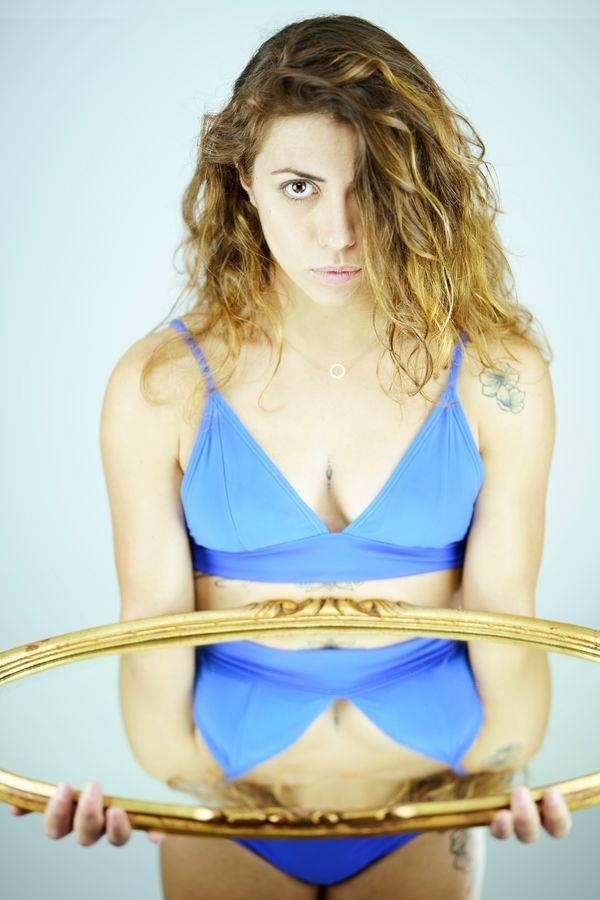 Portrait en studio d'Anaïs avec un miroir ovale  au cadre doré. Son maillot de bain bleu vif se voit, alors dans la réflexion.