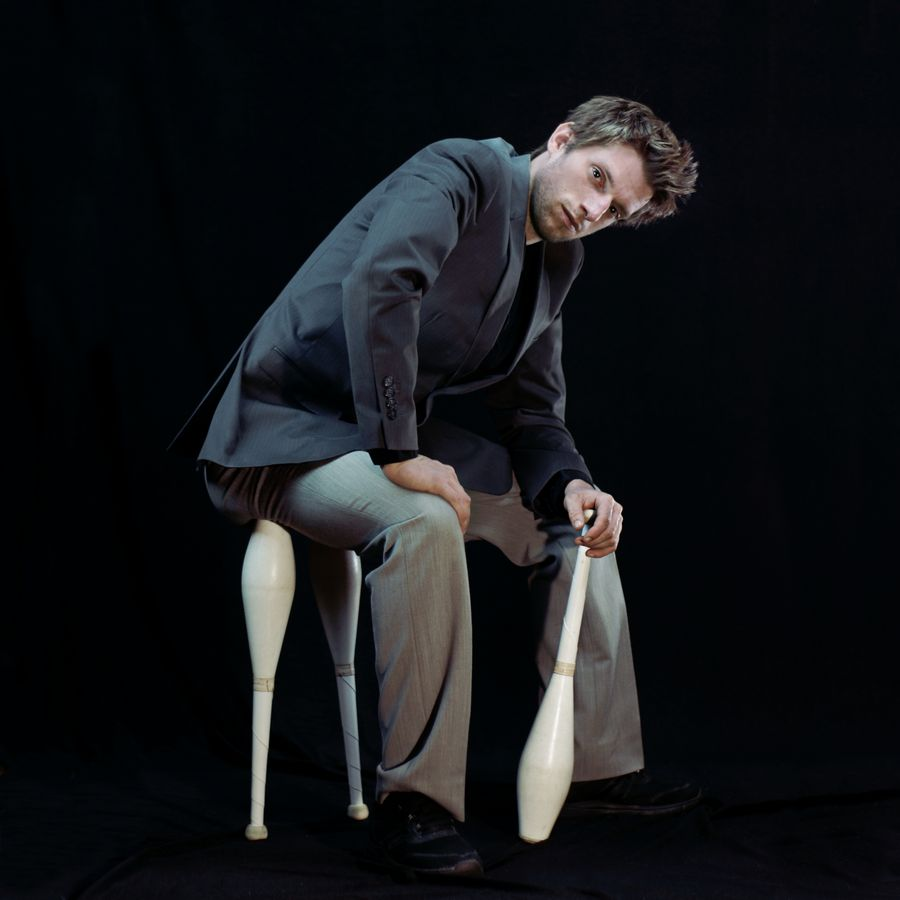 Portrait de Maxime assis sur ses massues, en studio à Caluire-et-Cuire. Il porte une tenue de ville et est penché en avant.