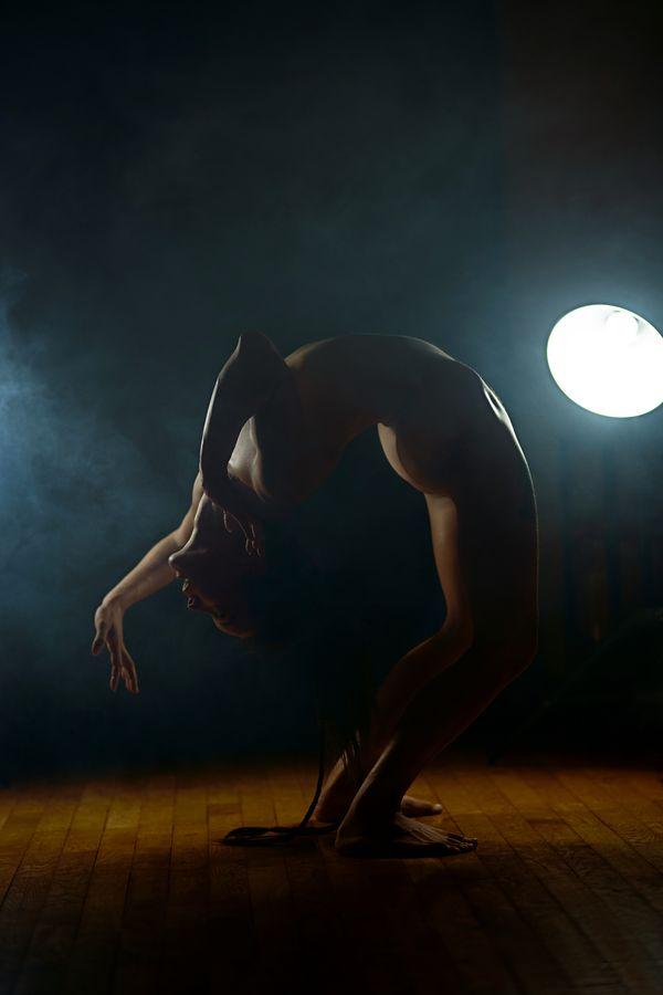 Annaïg fait une souplesse arrière, ou backbend en anglais, en studio à Caluire-et-Cuire. Elle maîtrise la figure et va lentement poser ses mains au sol.