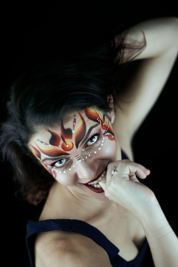 Portrait en studio de Juliette en train de se mordre un doigt. Elle arbore un magnifique maquillage réalisé par ses soins.