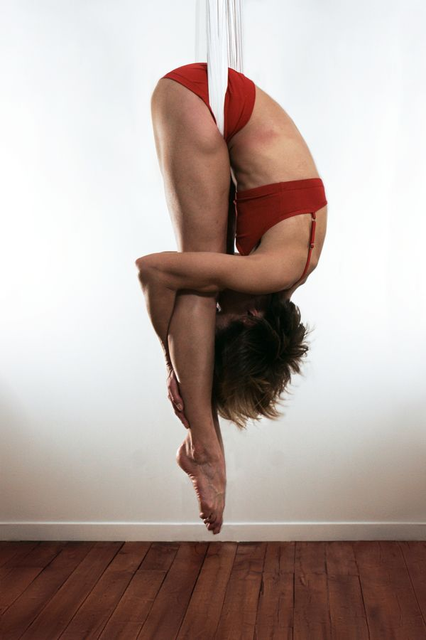 Sydney Martinie, tout en souplesse est complétement pliée en deux. Elle est suspendue dans son berceau de yoga aérien, chez elle, dans son salon.
