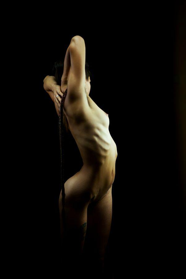 Annaïg fait un étirement en torsion, en studio, chez moi, à Caluire-et-Cuire. Son corps et à la fois extrêmement musclé et féminin.