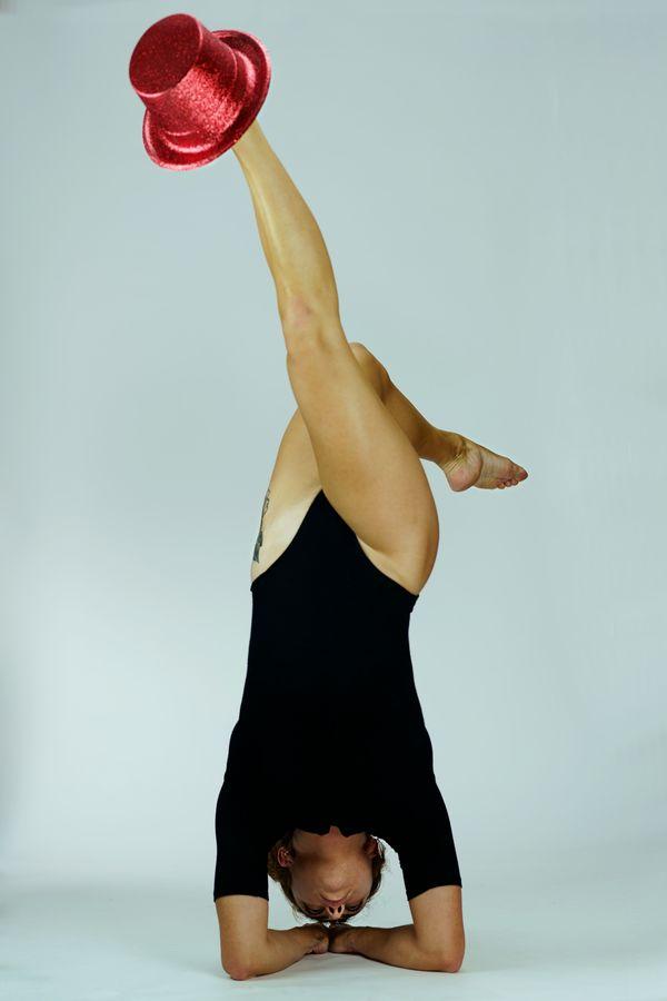 Anaïs est en équilibre en trépied avec un haut-de-forme rouge à paillettes au bout de pied. Le cliché a été pris devant un fond blanc à Caluire-et-Cuire.