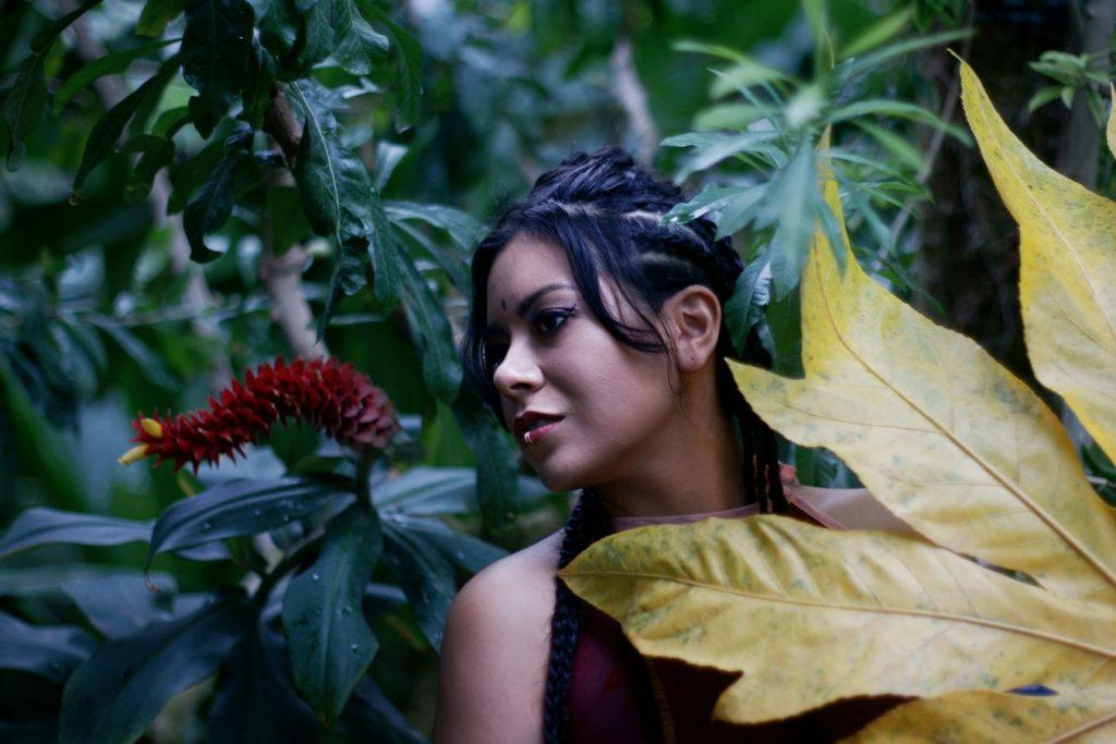 Portrait d'Ana dans les serres tropicales du Parc de la Tête d'Or, à Lyon. Elle est située entre une immense feuille jaune et une fleur rouge et jaune
