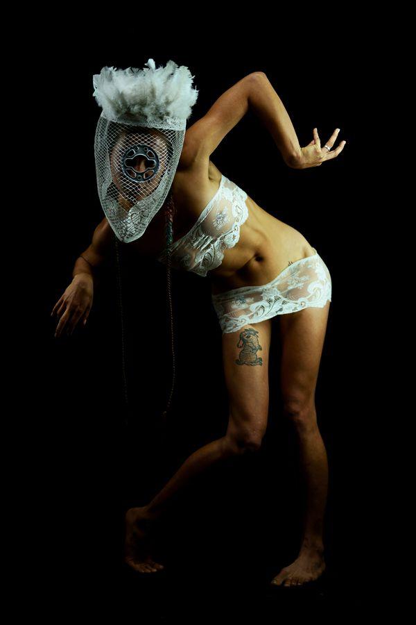 Portrait en studio, sur fond noir d'Annaïg en vêtements de dentelle. Elle porte un masque tribal avec des plumes fait à partir d'un ventilateur.